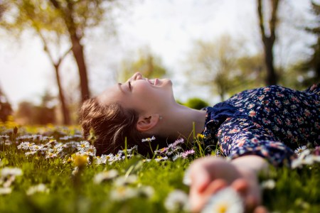 Pretty young teenage girl laying on a grass